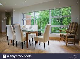 glass dining table and leather chairs in front of large window in