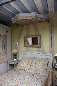 this rustic tudor style home will make you want to move to france in the master bedroom the cozy bed is a family heirloom and the mirror