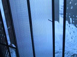 bronze front pivot door in a glass wall ref doors swimming pool