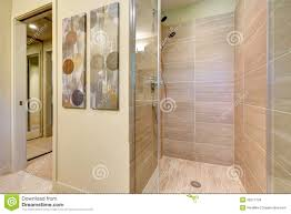 bathroom shower with glass doors and natural color tiles stock