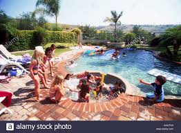 kids playing in backyard swimming pool and jacuzzi stock photo