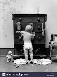 stock bureau 1940s toddler baby pulling clothes out of bureau drawers a