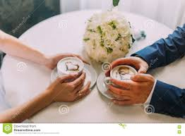 young couple warming their hands by coffee cups at the table in