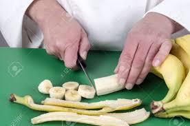 coupe banane cuisine chef féminin coupe une banane avec un couteau de cuisine banque d