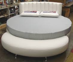 round grey bed frame with white leather headboard completed by