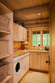white washed pine cabinets logs add a decorative touch to the main level laundry room which