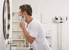 a young man is shaving his face in front of the bathroom mirror