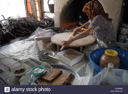 turkish woman making flat bread in fireplace in home near village