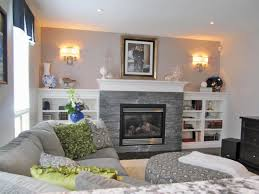 this neutral living room features a gray stacked stone fireplace
