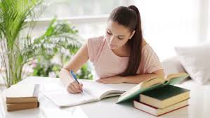Picture Of Student Sitting At Desk Bored Student Sitting At Desk Writing In Workbook And Looking