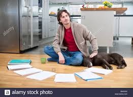 Dogs On Laminate Floors Mid Man Doing Paperwork On Floor While Dog Is Sleeping Next