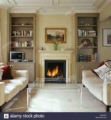Cream Bookshelves by Lighted Fire In Fireplace Between Fitted Bookshelves In Modern