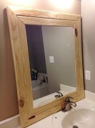 square mirror with brown wooden mirror frame leaning on brown wall