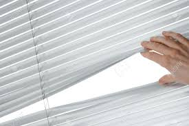 female hand separating slats of venetian blinds to see through
