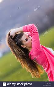 side view of pulled back hair in a bun looking back over shoulder female teenager outdoors pulling pull
