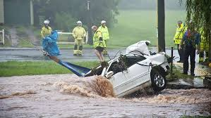 Courier Mail. A car is pulled out of the water