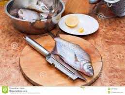 raw fish on wooden cutting board with knife in the kitchen stock