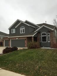 good looking dark gray siding with red brick grey craftsman two story