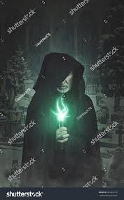 dark halloween background dark portrait hooded wizard graveyard background stock photo