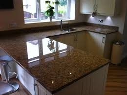 granite countertop light wood floors with dark kitchen cabinets