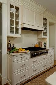like hood over range with glass front cabinets flanking hood like