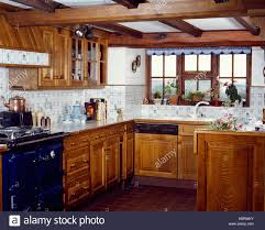 country kitchen with wooden cupboards and blue and white wall