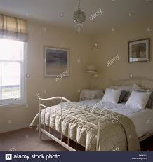 beige silk quilt and white bedlinen on cream metal bed in simple