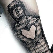 man with shaded black musical notes and heart tattoo on wrists for
