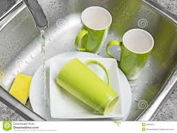 Green Kitchen Sink washing green cups and plates in the kitchen sink stock image