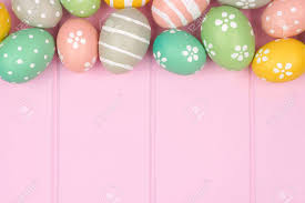 pink easter eggs pastel easter egg top border against a pink wood background stock