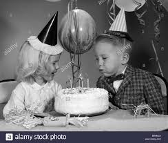 1960s boy blowing out candles on birthday cake stock photo