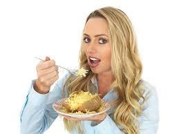 femme de chambre chaude femme d une chevelure mangeant une pomme de terre en