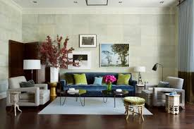 living room flower in the left side and painting on the wall and on the wall and flower pot in the table and blue sofa with some cushions also standing lamp in both sides apartment living room decorating ideas
