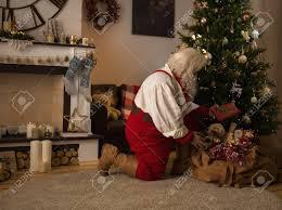 santa claus putting gifts tree at home stock photo