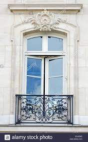 a grand window opens onto a wrought iron balcony in paris stock