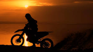 on road motocross bikes off road motorbike extreme cornering motorcyclist at sunset near