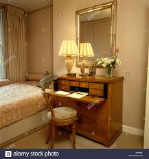 Lighted Desk Mirror Above Antique Desk With Lighted Lamp In Neutral Guest Room