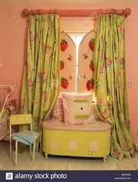 Pink Bedroom Cushions - cushions on lime green chest below window with pink green curtains