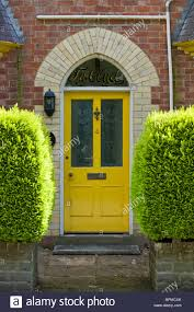 victorian paneled and glazed yellow painted front door of brick