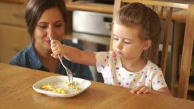 une mère heureuse alimente une fille la maman joue une fusée