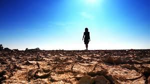 barefoot woman walks through surreal desert land landscape