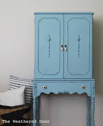 a long legged light blue cabinet the weathered door