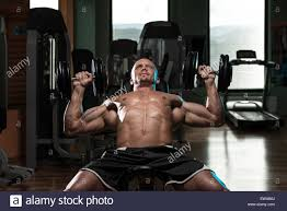handsome young man doing dumbbell incline bench press workout in