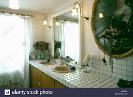 mirror above double basins in tiled vanity unit in white bathroom