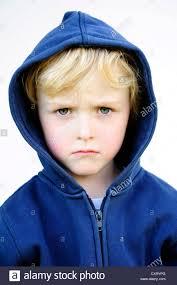grim faced 5 year boy wearing a hoodie jacket portrait stock
