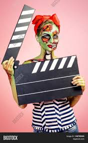 halloween pink background pin up zombie woman holding clapperboard over pink background