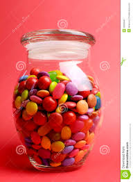 glass jar full of bright colorful lollies and candy with closed