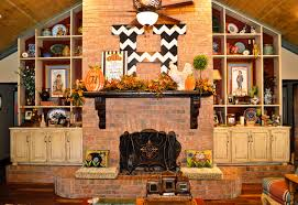 the fall fireplace mantel is completed with a harvest sign and metal pumpkins