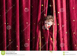 impatient young actor peeking out from the curtain stock photo