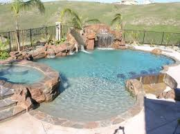 Backyard Pool With Slide Swimming Pool With Waterfall Grotto Slide And Sunken Bar